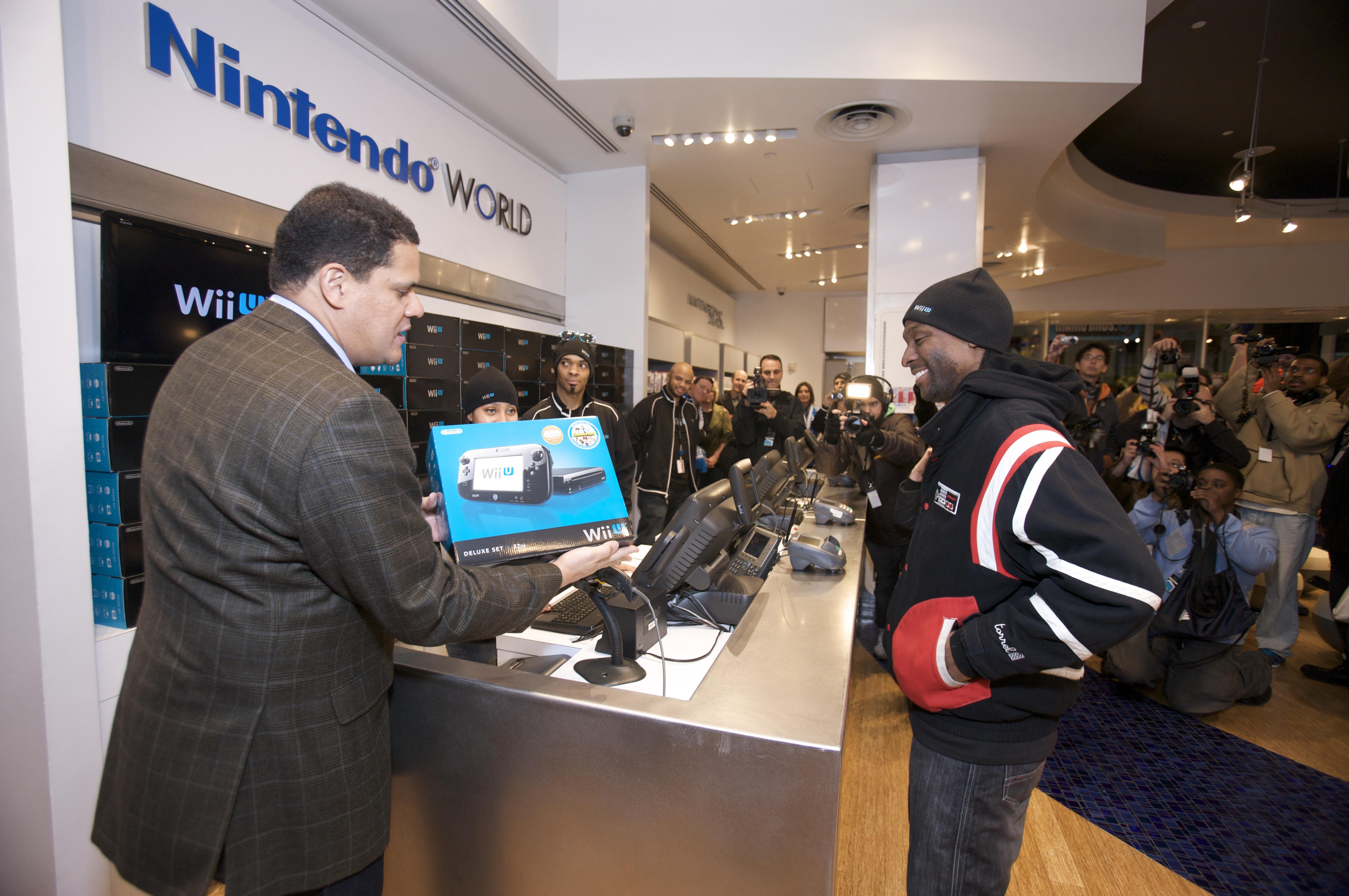 Reggie entrega el primer Wii U del mundo a Isaiah Triforce Johnson de Brooklyn. Muchos pensaron que Johnson había perdido el primer lugar en la fila, después de que los fanáticos fueran evacuados por la llegada del huracán Sandy.