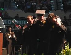 Graduating student rises from wheelchair