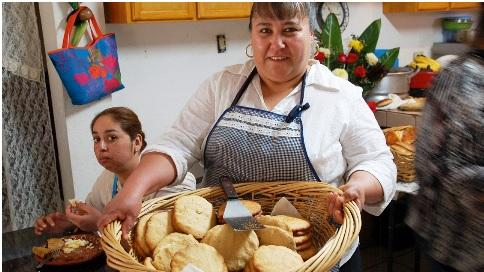 Doña Esthela delivers fresh-baked pan de elote to the kitchen.