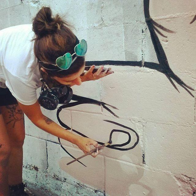 Panca painting the mural.