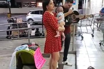 Pareja canta en la calle para obtener dinero y comprar leche para...