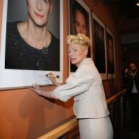 Tilda Swinton firmando su póster