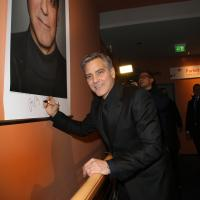George Clooney firmando su póster